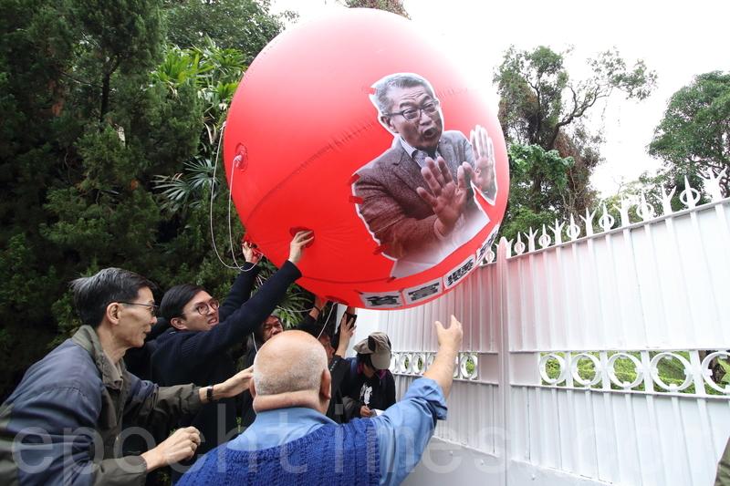 約10名社民連成員到昨日陳茂波官邸示威,要求政府在財政預算案中動用儲備改善港人生活。圖為示威者將貼一個貼有陳茂波肖像的紅色巨型汽球,推入官邸。(蔡雯文/大紀元)