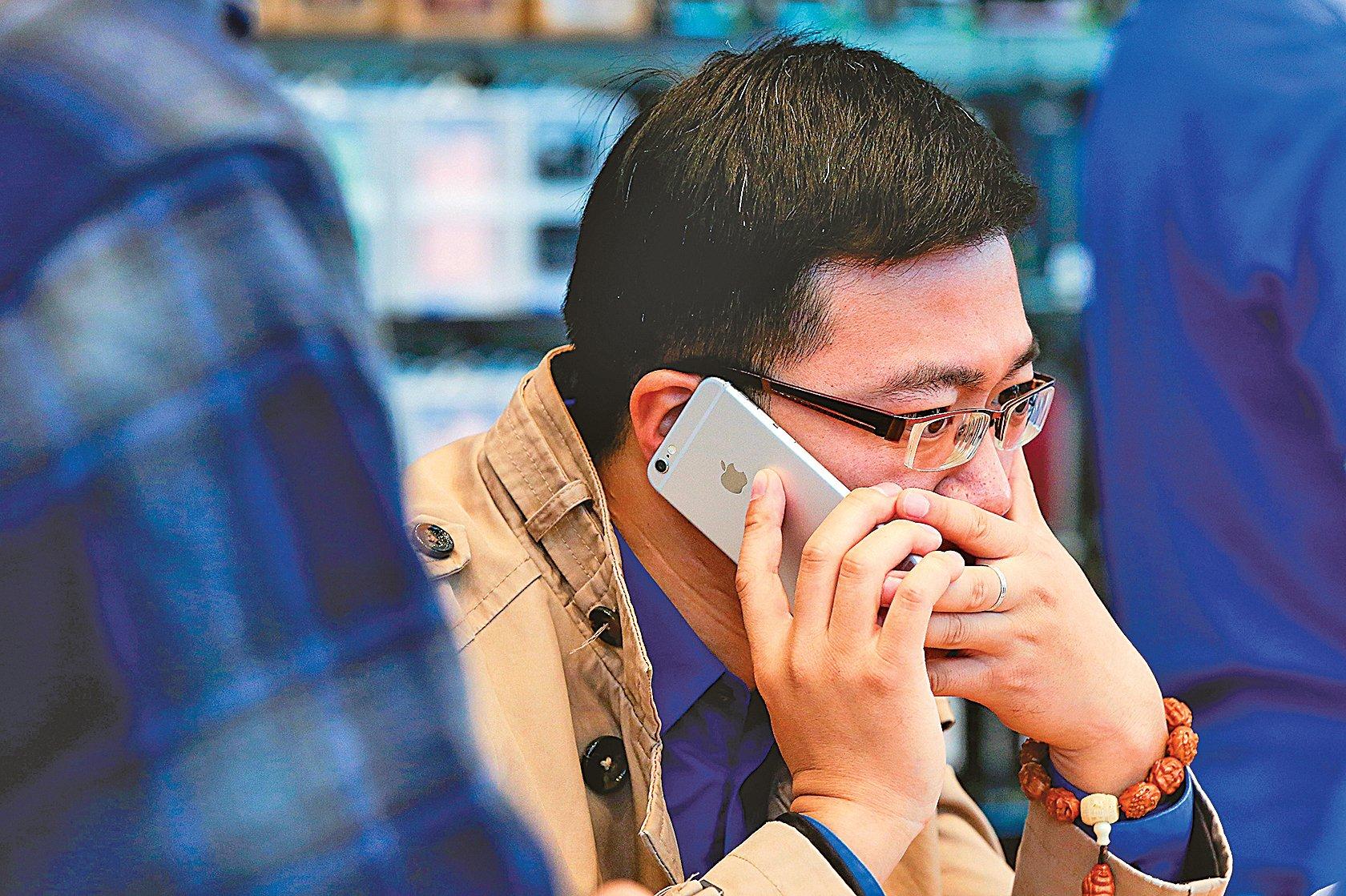 北京男子在蘋果店試用iPhone6。(Getty Images)