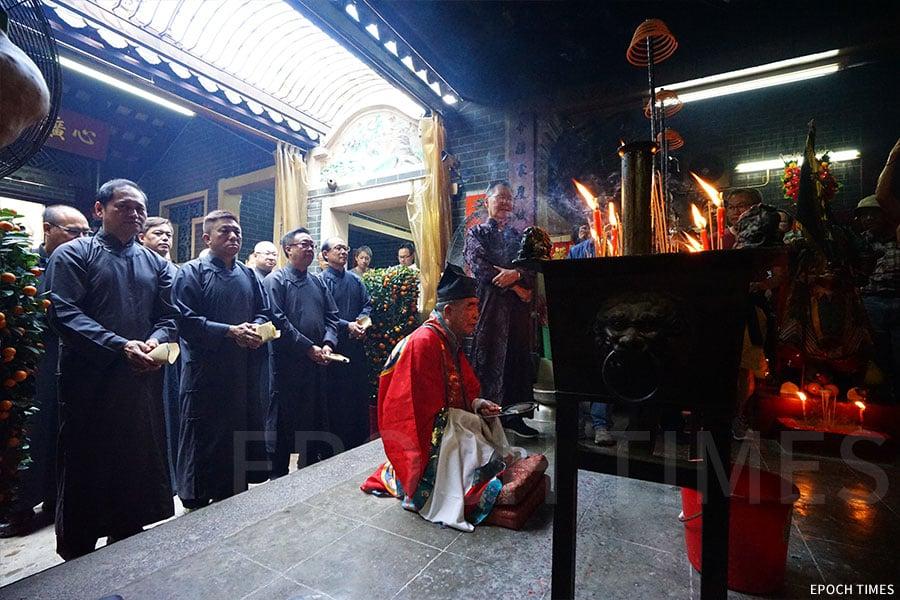開燈前,村民前往北帝廟請神,由喃嘸帶領「神頭」及一眾族人拜神。(曾蓮/大紀元)