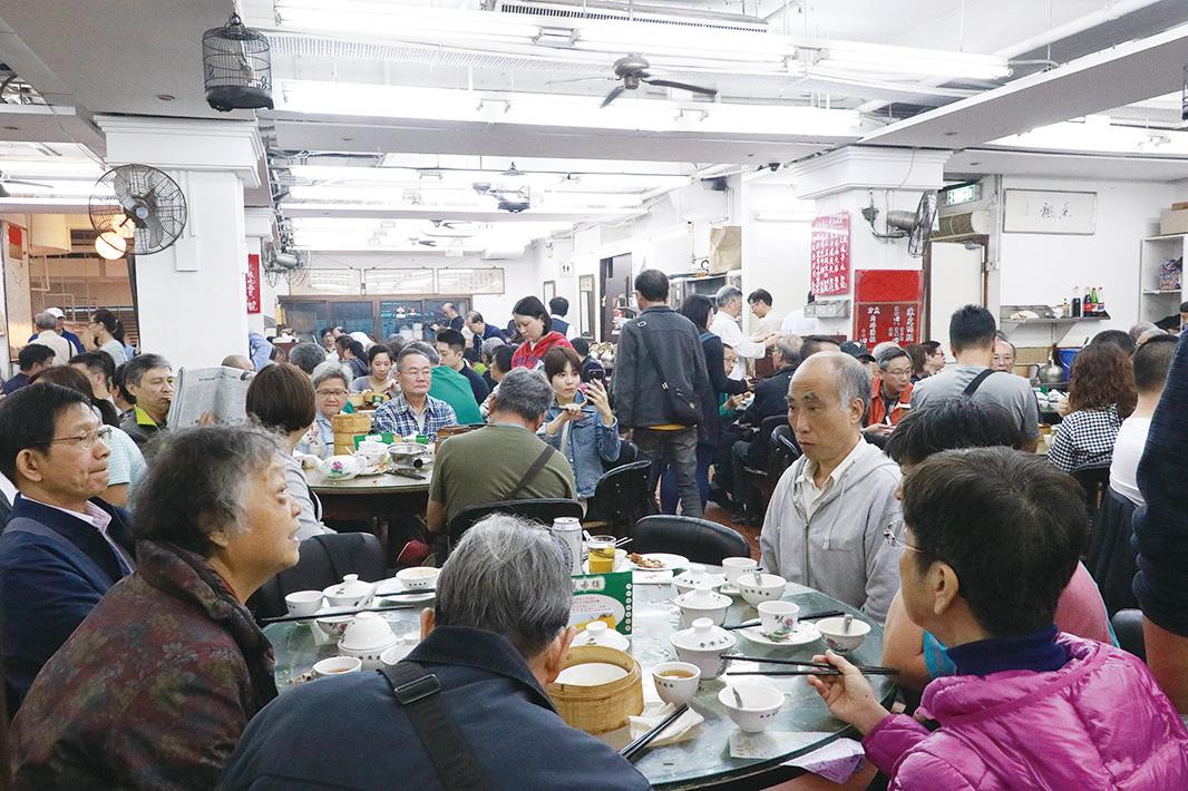 茶樓雖然人聲吵雜,但食客們自得其樂, 陌生人圍坐一齊,「搭枱」食飯。