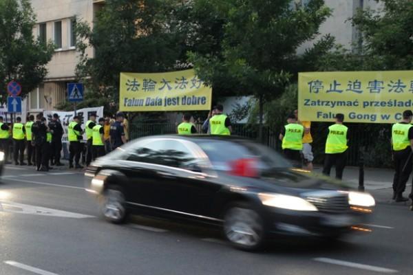 6月19日晚,波蘭法輪功學員在習近平下榻的Hyatt飯店前,手持橫幅和平請願。(Tomek O/大紀元)