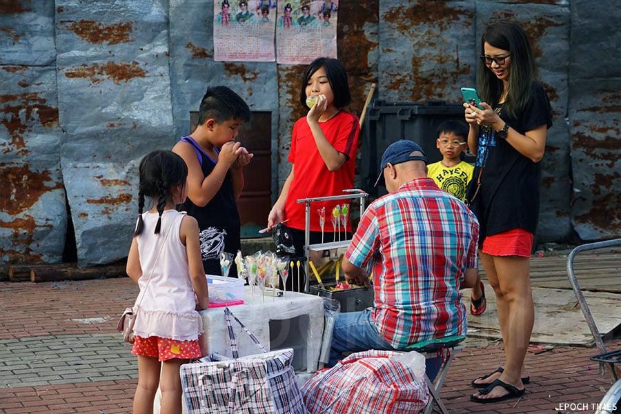吹波糖檔口吸引了不少家長和小朋友圍觀與玩樂。(陳仲明/大紀元)