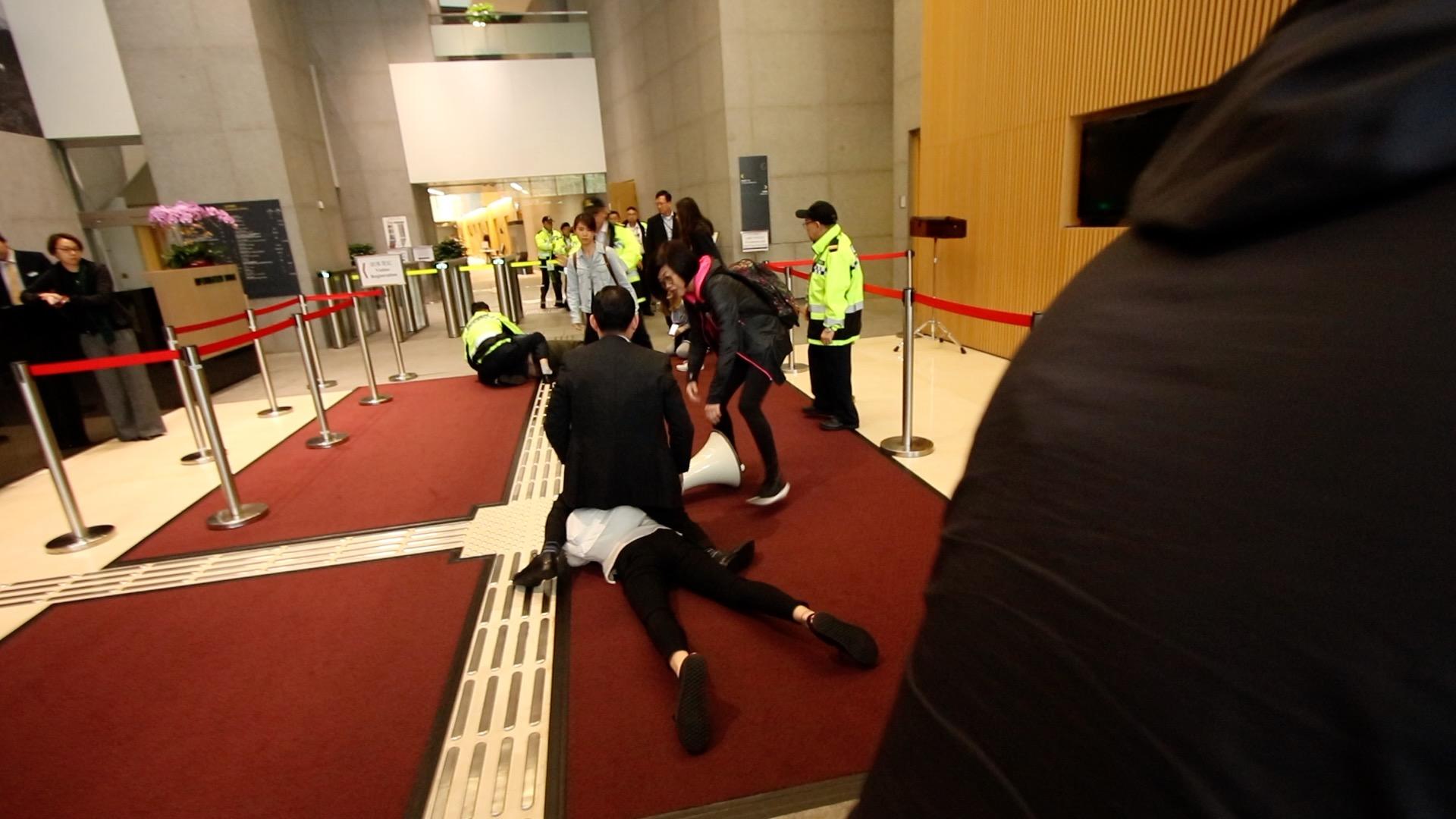 一名政總男保安騎在香港眾志女成員何嘉柔身上。(蔡雯文/大紀元)
