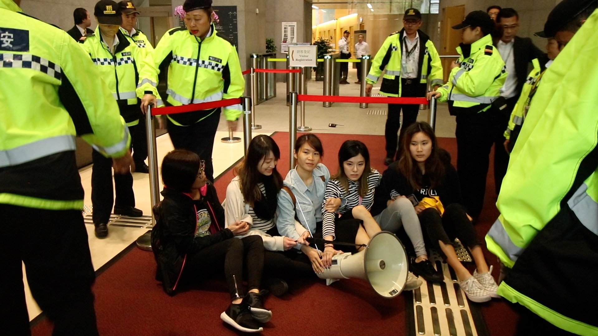 何嘉柔(左二)與其他示威者靜坐在政府總部大堂(蔡雯文/大紀元)