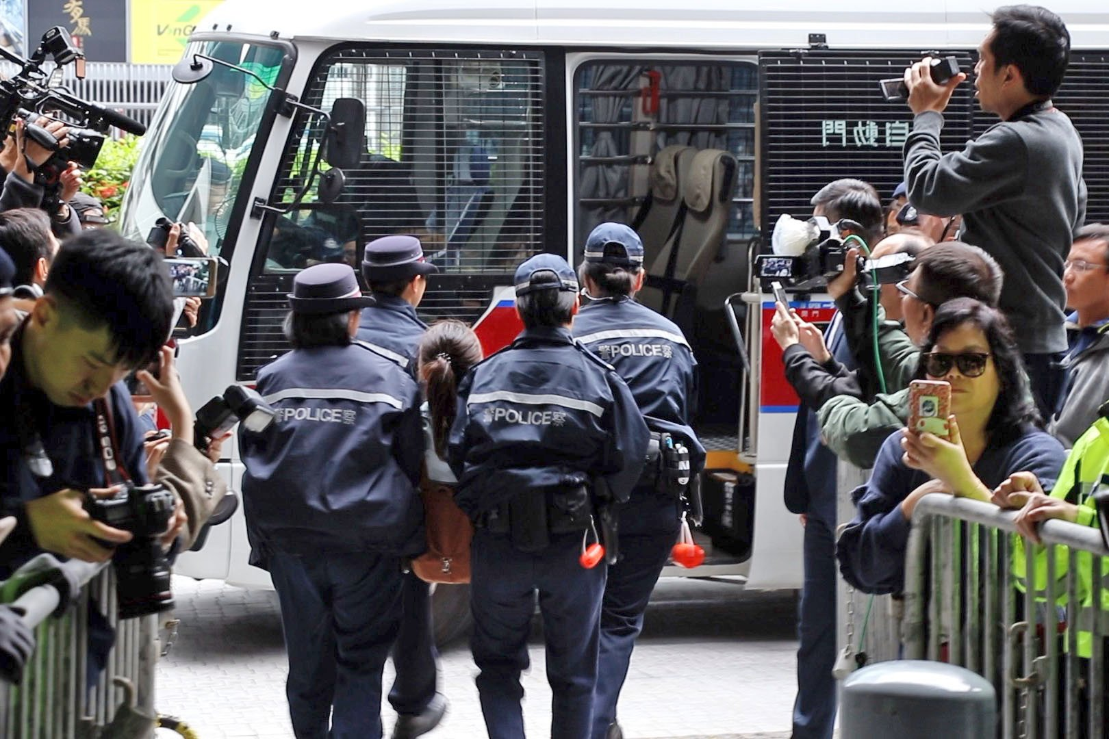 香港眾志等9名成員被抬上警車帶走。(蔡雯文/大紀元)