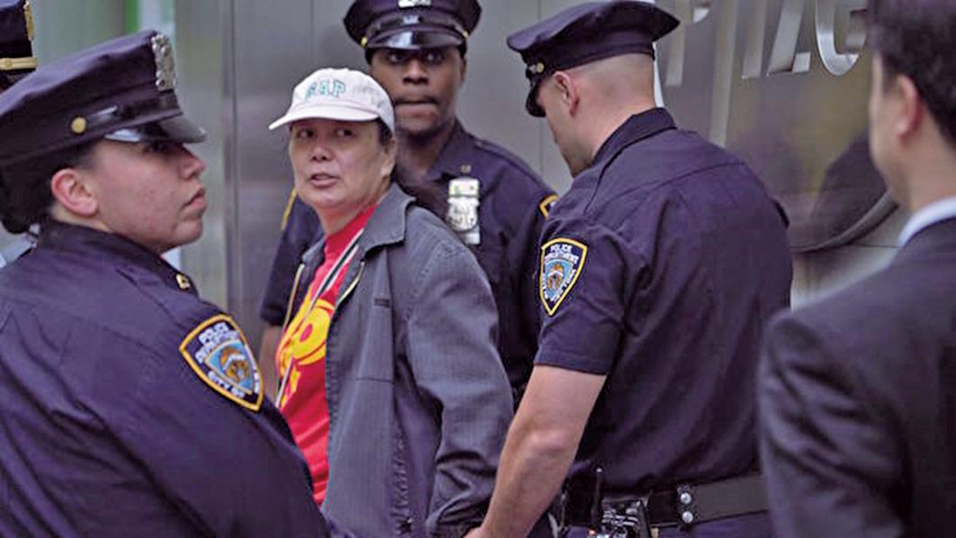 2016年5月13日,李華紅(中)因為干擾法輪功活動被紐約警察當場拘捕。(大紀元)
