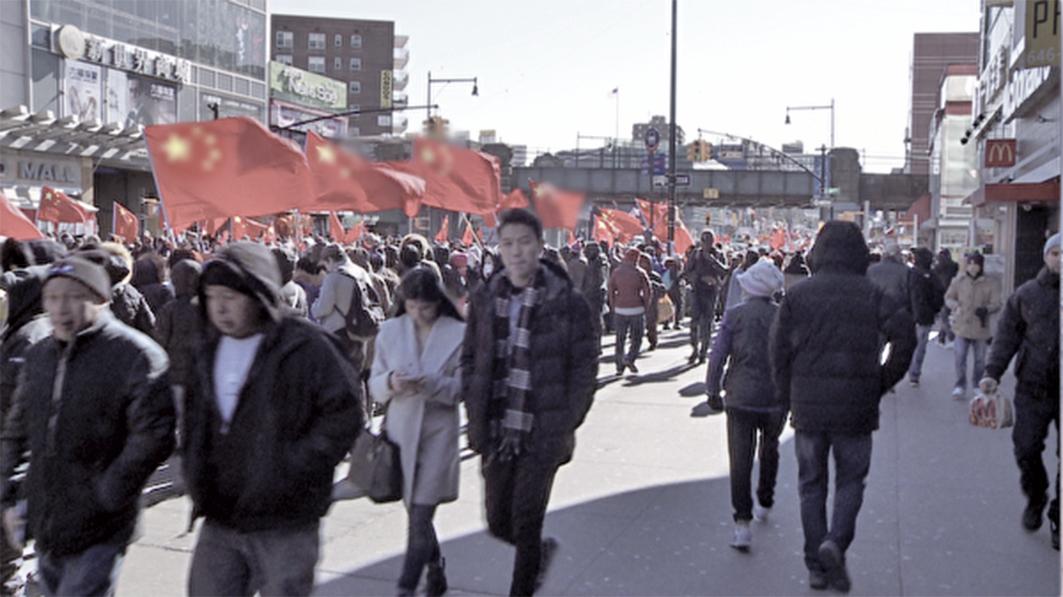 2019年2月9日,法拉盛新年大遊行,李華紅組織人員用中共紅旗「佔領」街頭。(大紀元)