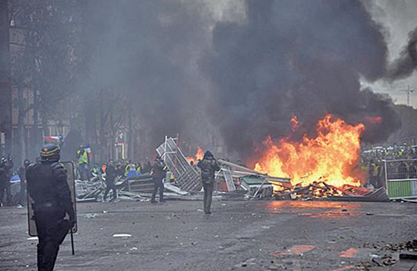 2018年11月24日黃背心遊行示威者縱火,和警方在香榭麗捨大街上發生激烈的暴力衝突。(AFP)