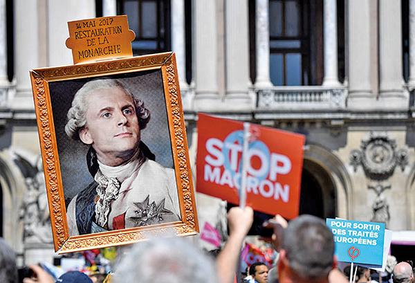 2018年5月5日馬克龍當選一周年,巴黎一遊行隊伍中有一圖片將馬克龍與路易十六做肖像合成,抗議政府復興「君主制」。(AFP)