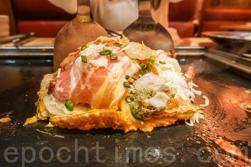 廣島燒煎熟椰菜和配料的同時,也要煎好炒麵,最後再將椰菜和配料放在炒麵上,再淋上醬汁。