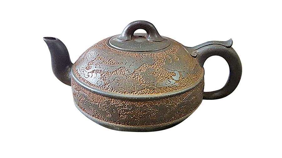 這把歷史悠久的紫砂壺,鳳在上、龍在下的紋飾獨一無二,不小心遺留在壺內的茶葉多年後不發霉不腐爛,足見老壺工藝之神奇。