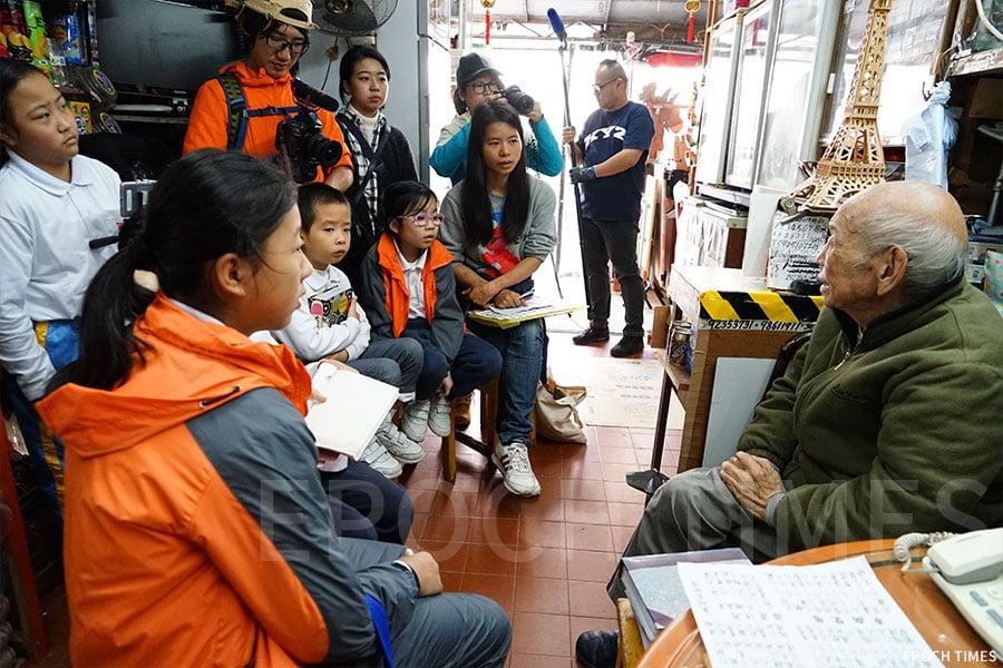 小記者採訪東京士多的九十二歲店主盧細喜。(曾蓮/大紀元)
