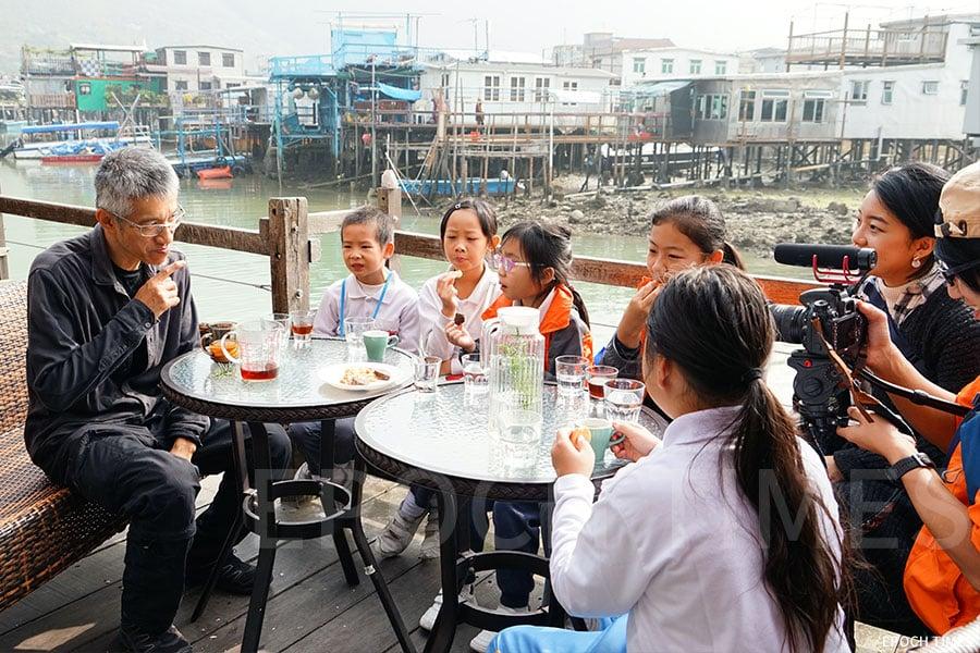 原生咖啡店蘇廬的蘇老闆與小記者分享趣事。(曾蓮/大紀元)