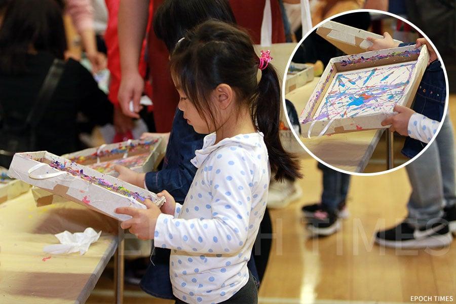 根據繪本《Colour Monster》設計的環保藝術手作攤位,孩子用圓球蘸上水彩在廢棄的Pizza盒內創作繪本中的角色。(陳仲明/大紀元)