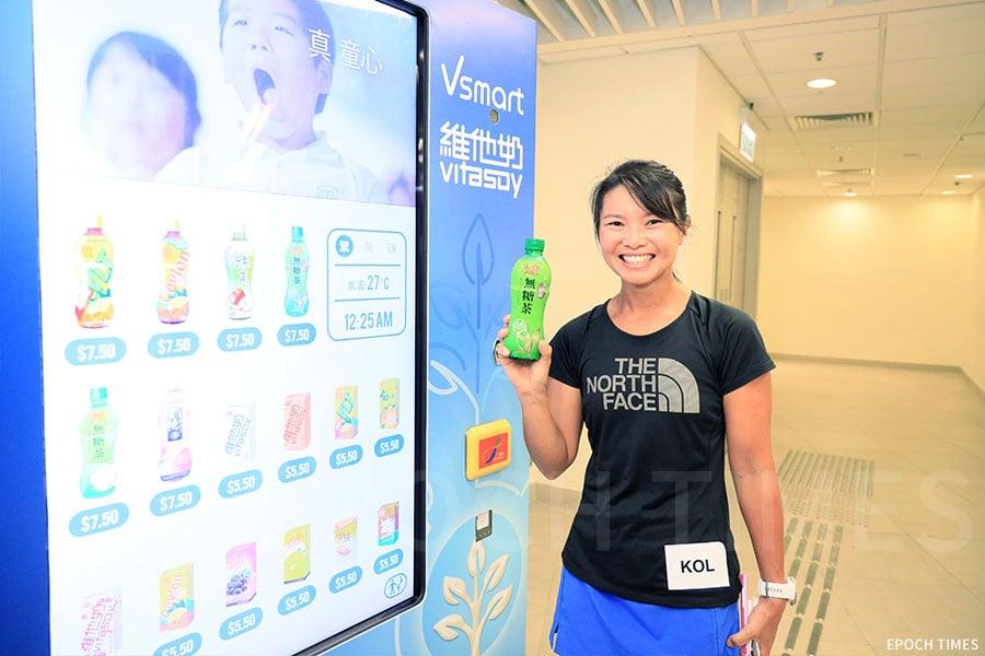 運動員兼教練周佩欣(Wyan)試用「Vsmart『維他奶』智能飲品售賣機」。(王偉明/大紀元)