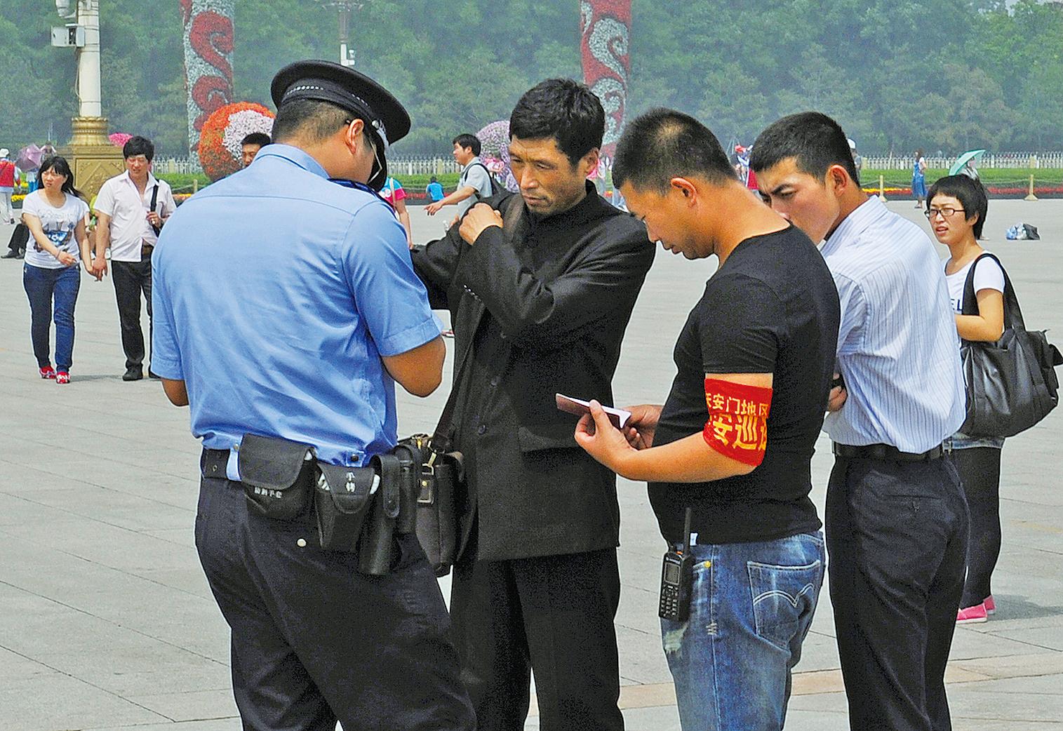第三代身份證加入了定位及收集個人指紋和血液信息等新功能。圖為2012年中共六四屠城23周年之際,北京警察在天安門廣場檢查一名男子的身份證並逮捕了他。(AFP)