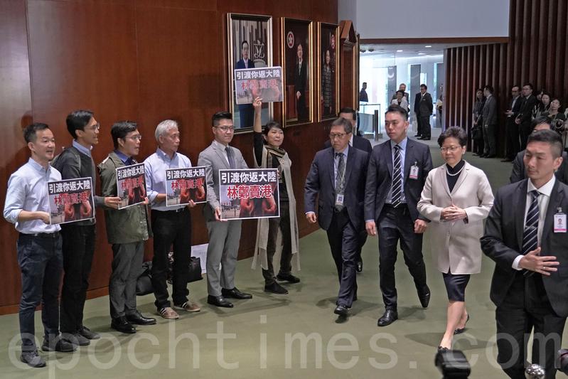 林鄭月娥進入議事廳時,議會陣線議員手持「引渡你返大陸」標語抗議及高叫口號。(李逸/大紀元)