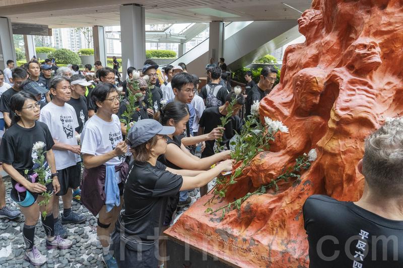 場默後舉行獻花儀式,眾人將一朵朵白色鮮花放到「國殤之柱」上。(李逸/大紀元)