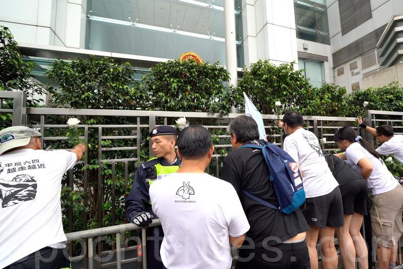長跑人士最後將把白菊花插在中聯辦的圍欄,結束今次長跑活動。(李逸/大紀元)