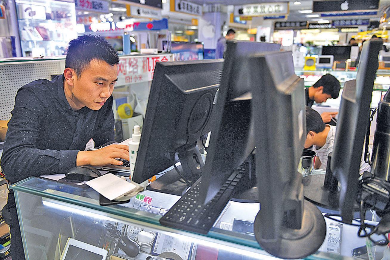 北京一名工作人員在修理筆記本電腦。(Getty Images)
