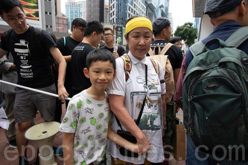 唐女士帶著10歲孫子上街。(蔡雯文/大紀元)