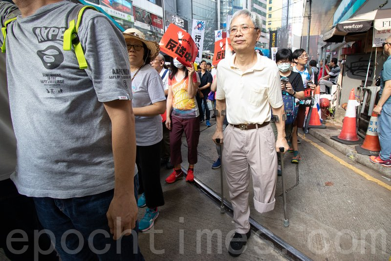 曾先生撐著兩個枴杖上街。(蔡雯文/大紀元)