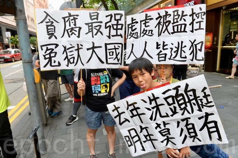 10歲的莊小朋友和9歲弟弟,在母親帶領下參加遊行,並自製展板。(宋碧龍/大紀元)