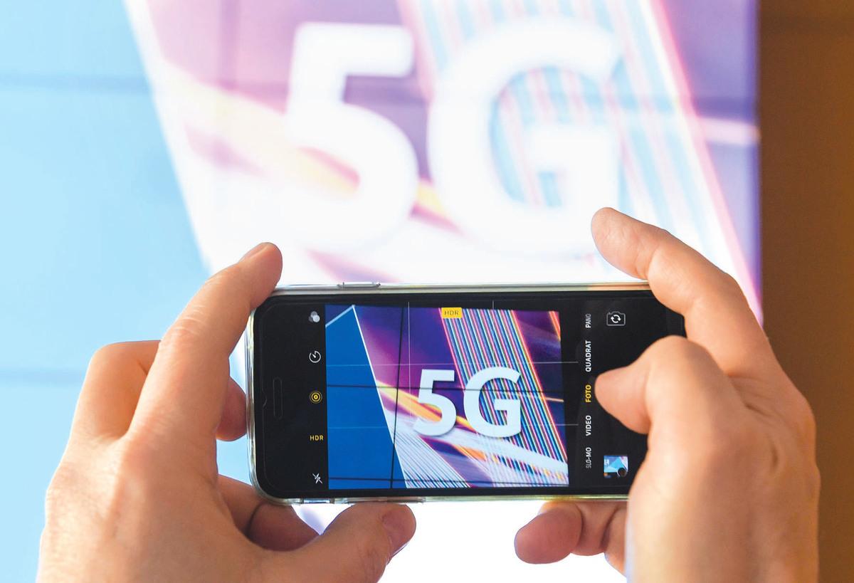 今年3月19日,德國5G頻譜拍賣開始前,一名記者拍攝帶有5G字樣的投影。(Getty Images)