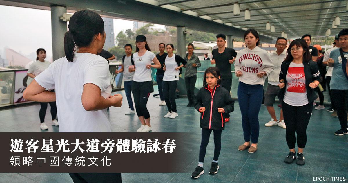 數十名中外遊客近日在尖沙咀星光大道李小龍像旁一起學習詠春。(王偉明/大紀元)