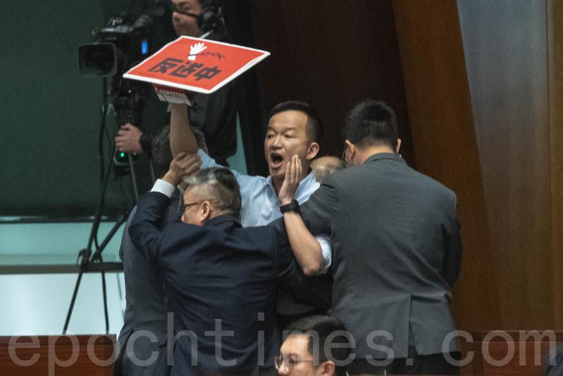 人民力量陳志全衝向前抗議,高喊「林鄭月娥下台」,也被逐出議事廳。(李逸/大紀元)