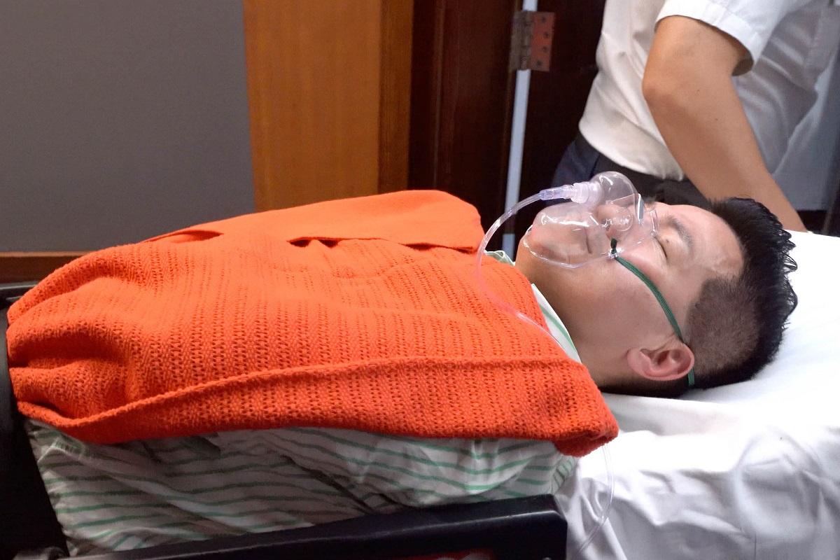 民主派議員范國威由救護員用擔架抬走,送往瑪麗醫院,目前正在留醫。(李逸/大紀元)