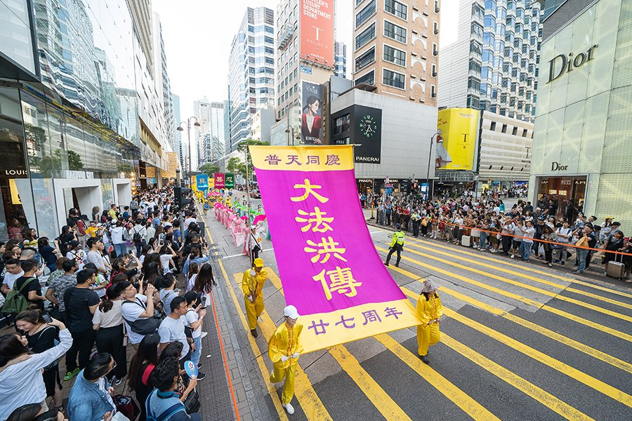 5月12日,香港法輪功學員舉行集會遊行慶祝世界法輪大法日。圖為遊行隊伍途經尖沙咀廣東道,大批遊客和市民夾道觀看,紛紛拍下盛大的遊行場面。(李逸/大紀元)