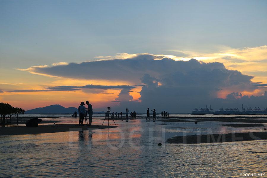 黃昏漸近,泥灘上的水漥也反映出晚霞的色彩,如詩如畫。(陳仲明/大紀元)