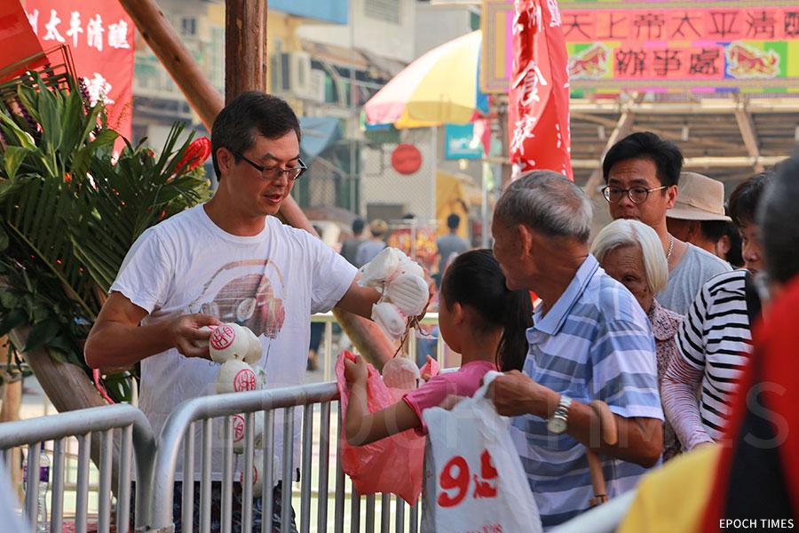 長洲太平清醮值理會總理鄺世來(左)在北帝廟前廣場幫忙派平安包。(陳仲明/大紀元)