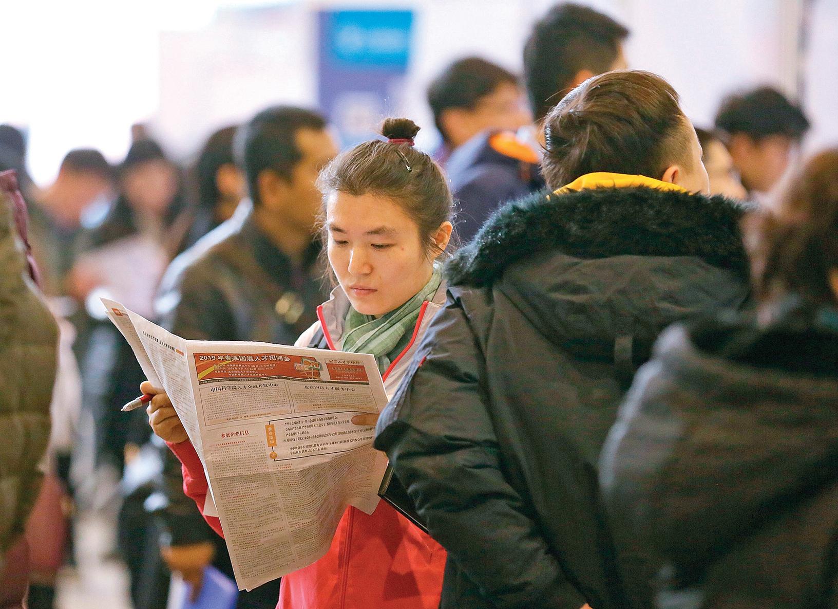 2月23日,北京的一個春季人才招聘會上應聘人員瀏覽招聘材料。(大紀元資料室)