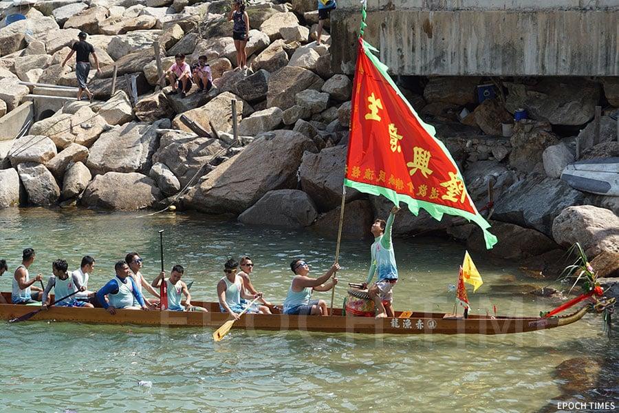 主辦單位向參與賽事的龍舟隊頒發大旗,向各隊送上祝福,為參賽隊伍打氣。(曾蓮/大紀元)