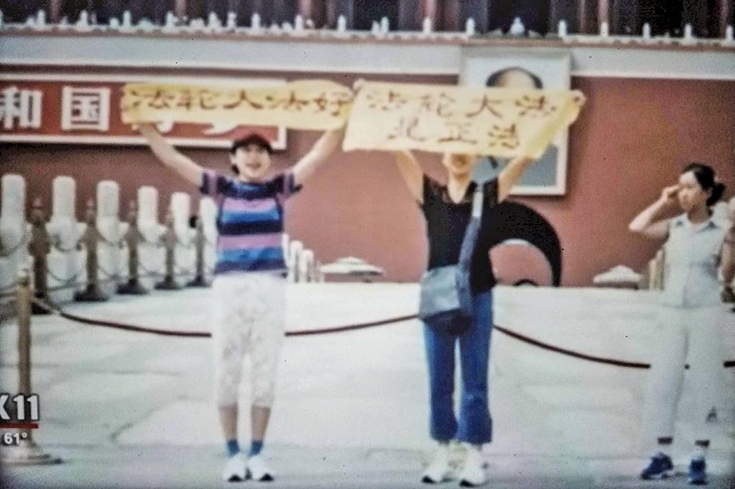 2001年,王可非和姐姐王易非在天安門廣場舉著「法輪大法好」和「法輪大法是正法」的橫幅。(明慧網)