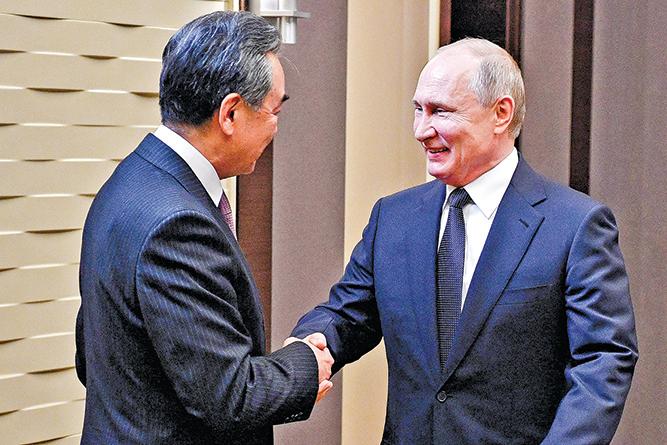 俄羅斯總統普京(右)上星期會見中共外長王毅(左)。(AFP)