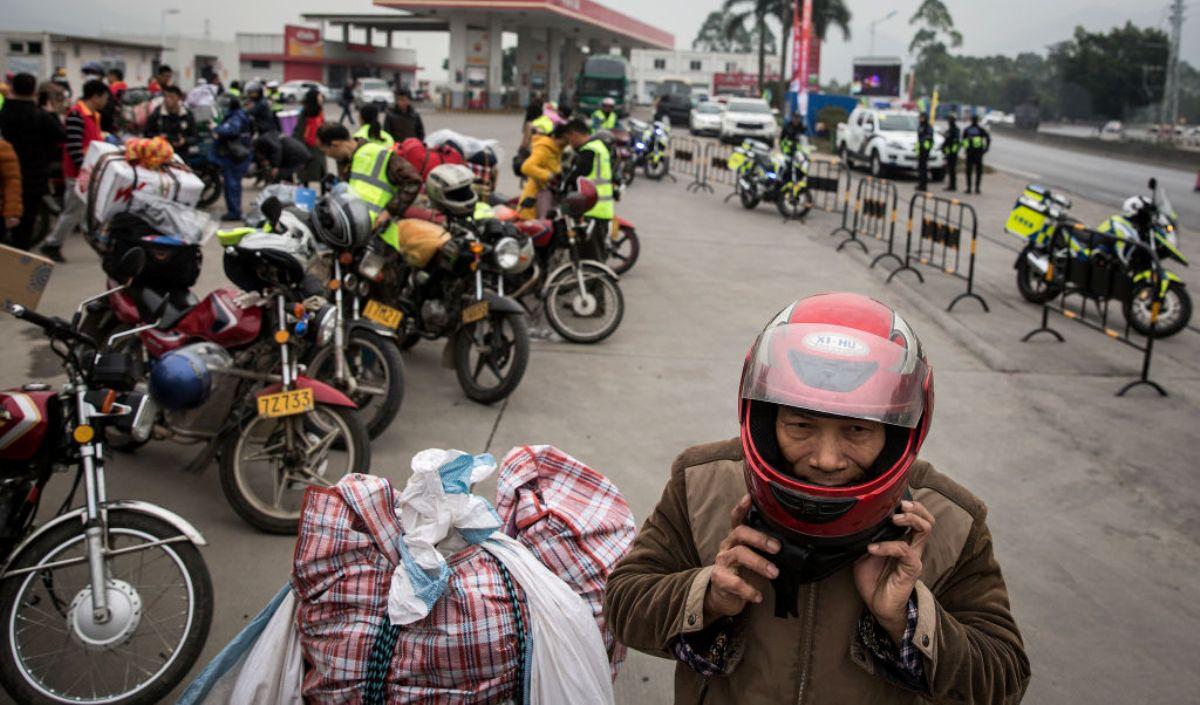 圖為一些騎電單車攜帶行李返鄉的中國農民工2019年1月25日在廣東省肇慶市一間加油站加油休息。(Wang He/Getty Images)