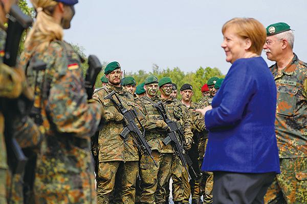 德國軍方正在調查3名大陸記者,懷疑他們在德國總理默克爾(前右一)訪問北約軍事基地時蒐集情報。(Morris MacMatzen/Getty Images)