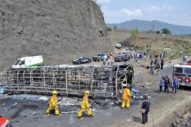 墨西哥東部29日一輛半掛式卡車和一輛巴士相撞後起火燃燒,警消撲滅火勢後,車子被燒得僅剩車架。(Getty Images)