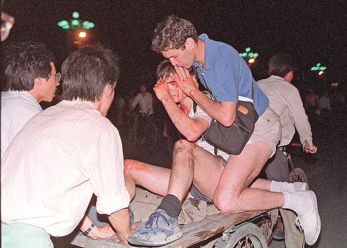 30年前的6月4日,不少外國記者也成為那一夜中共軍隊對民眾血腥鎮壓和屠殺的見證人,他們也見證了學生們如何勇敢地幫助傷者並帶他們撤離現場。(AFP)