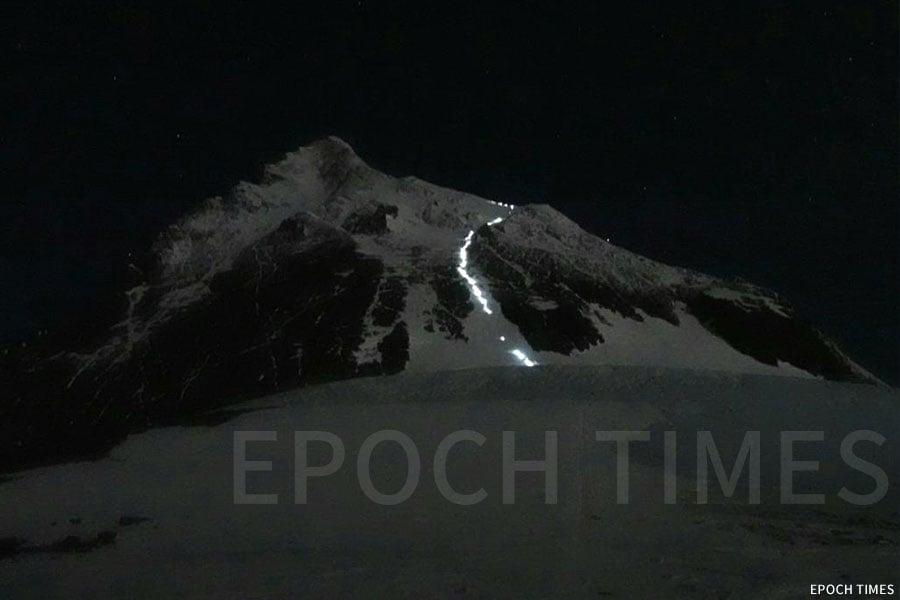 夜間攀登珠峰者的燈光在珠峰上構成一條光帶。(公關提供)