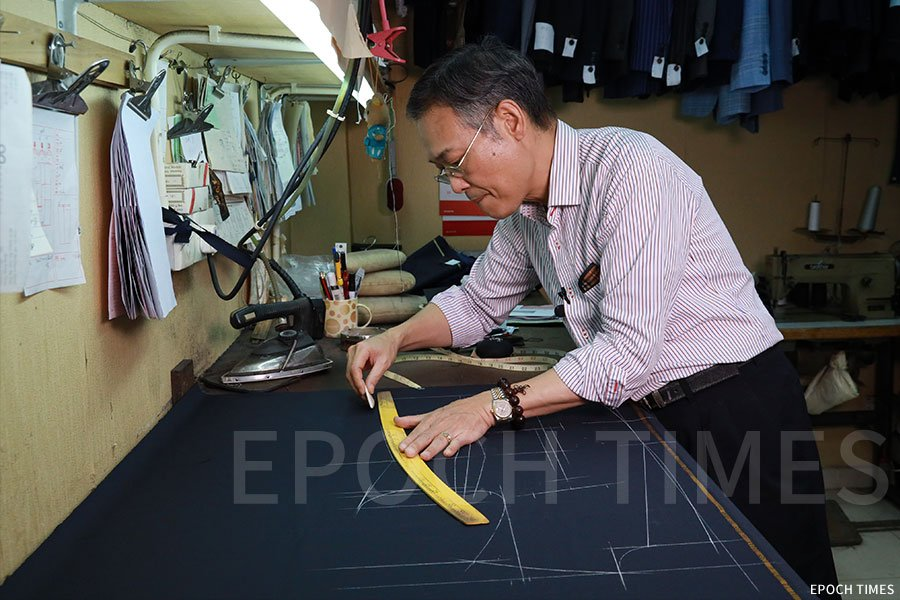 洪師傅為客人量度出尺寸,便能在面料上畫出衣服的版型。(陳仲明/大紀元)