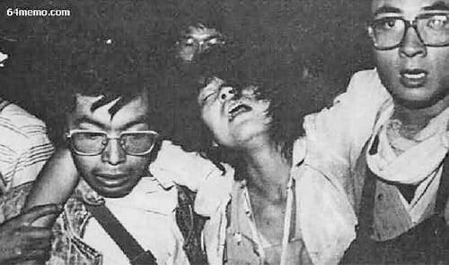 中共軍隊開始向廣場上的學生開搶,幾位男同學扶著一位受傷女同學趕往醫院。(六四檔案網)
