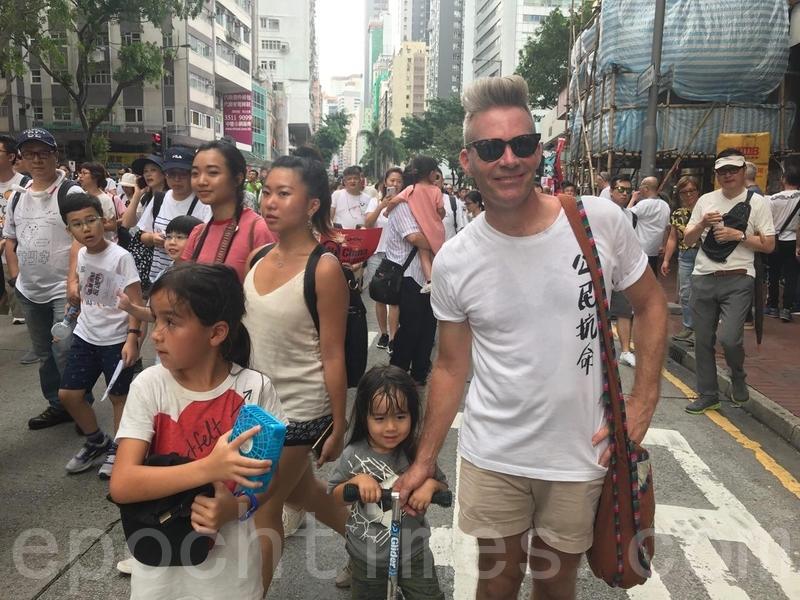 Brian Kern與妻子和兩位女兒一起上街遊行。(王文君/大紀元)