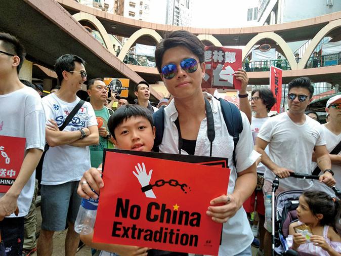 鄺先生與9歲的兒子一起遊行。(林怡/大紀元)