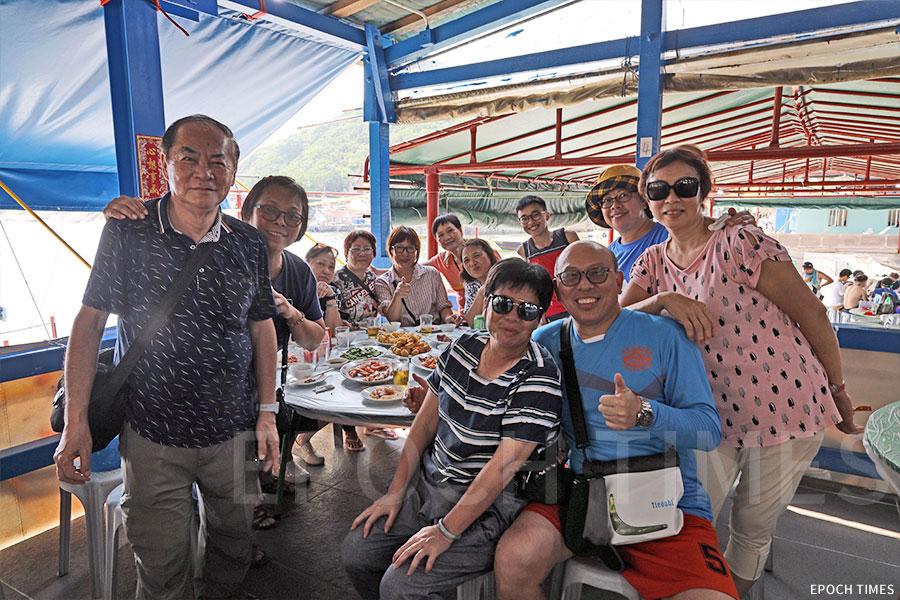 張啟勳老師(左一)與學生們的關係頗佳,每年天后誕均會回到島上與學生們相聚。(陳仲明/大紀元)
