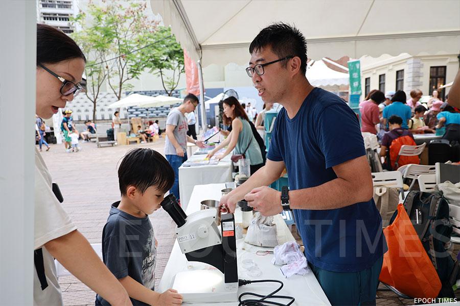 「水口放大鏡」項目負責人黃先生向家長與小朋友介紹微塑膠給人類帶來的危害。(陳仲明/大紀元)