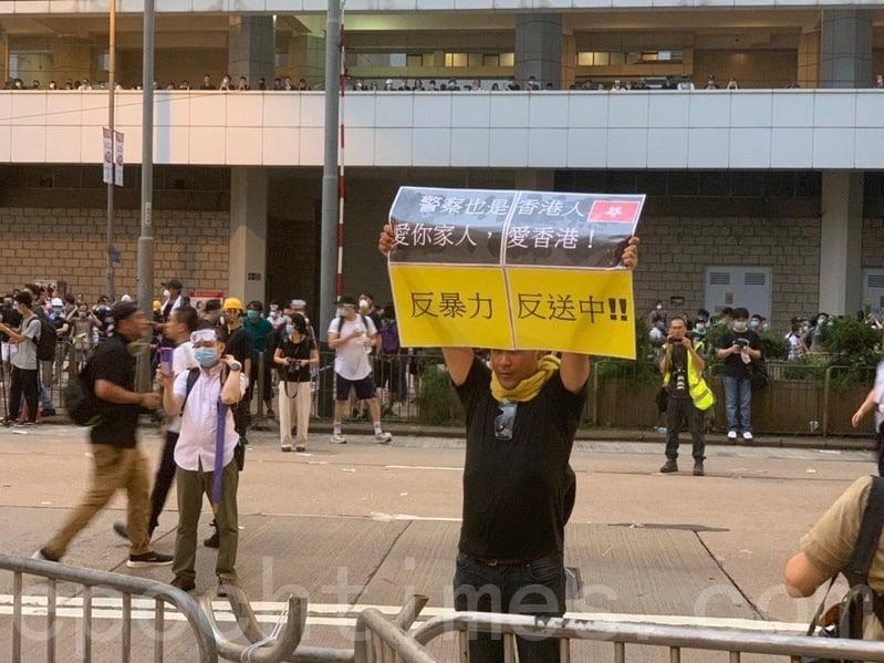 有民眾舉起「警察也是香港人,愛你家人,愛香港!反暴力 反送中」的標語,呼籲警方勿對群眾施暴。(李逸/大紀元)
